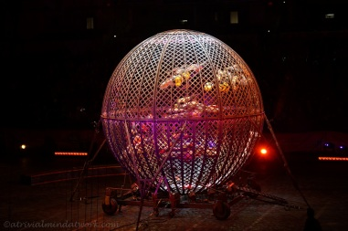Motorcycles riding around inside a spherical steel cage.
